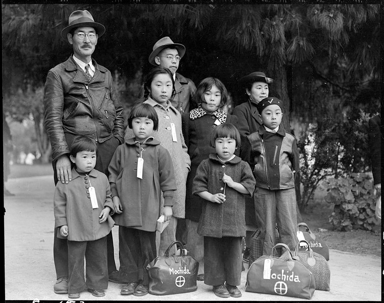 Members of the Mochida family awaiting a removal bus. Identification tags were used to aid in keeping the family unit intact during all phases of removal. May 8, 1942, Hayward, California. - COURTESY OF THE OAKLAND MUSEUM OF CALIFORNIA