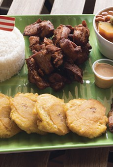 Combination meals are generously portioned, such as this chicharrones plate with tostones, beans, rice, and extra maduros.