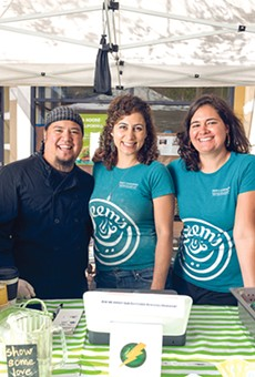 Jamal Jimenez (left) and Zaynah Hindi (right) work with Reem Assil (center) at her farmers' market stand.
