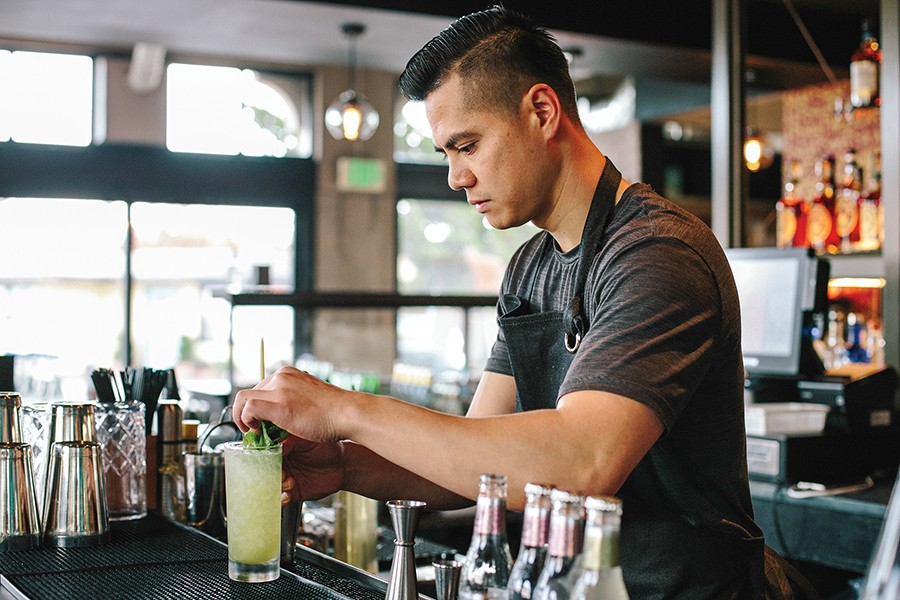 Owner Thomas Manyvong serves a cocktail made with lemongrass-infused gin. - MELATI CITRAWIREJA