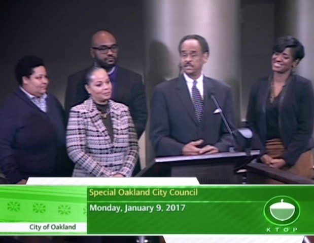 Taj Reid stands behind his father Larry Reid at an Oakland City Council meeting in 2017.