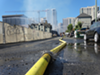 A hose runs water to the site of today's fire in Oakland's Broadway-Valdez area.