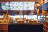 The noodle making is quite interesting to watch. A backlit menu shows Marugame's dishes.