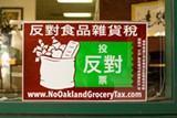"An poster presenting Oakland's ""soda tax"" as a ""grocery tax"" posted on a storefront window in Chinatown."