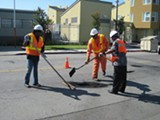 "NATE SELTENRICH - Workers repair a pothole during Oakland's recent ""pothole blitz."""