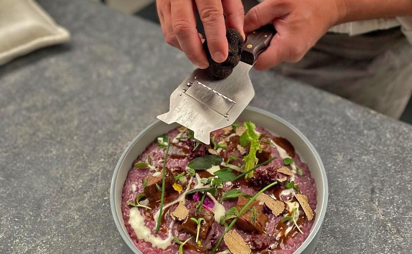 Chef Maurizio Ferrarese shaves truffles over risotto with Barolo wine.