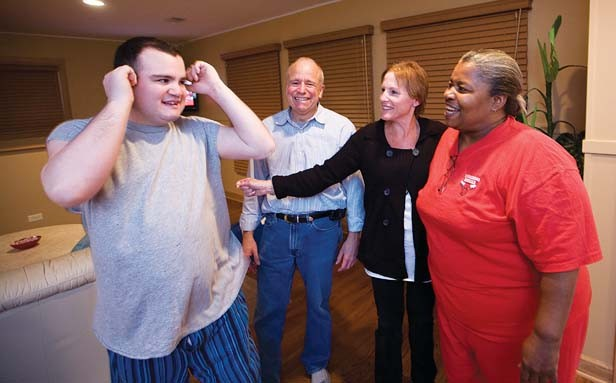 Eric Markin, an autistic 22-year-old, with his parents and his house manager. Advocates are giving more attention to autistic adults' needs, including housing and employment. - PHOTO BY CHARLES CHERNEY/MCT