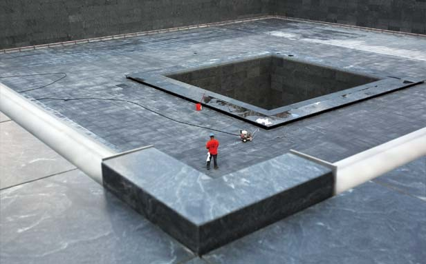 A construction worker stands in the form of the south pool at the National Sept. 11 Memorial in New York City. Bronze panels that ring the memorial's two pools bear the names of all 9/11 victims, as well as those who died during the 1993 trad - PHOTO BY SCOTT STRAZZANTE/MCT