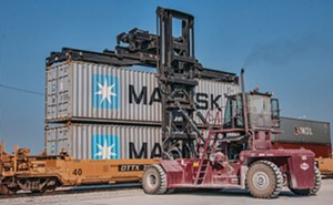 A crane loads a rail car with standardized shipping containers destined for a U.S. coastal port, where they will be loaded onto cargo ships and sent abroad. - PHOTO COURTESY ADM