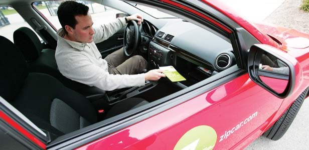 Adam Brophy, of Cambridge, Mass., reaches for the Zipcar Co-Pilot (Zipcar instruction manual) in the glove box of a 2007 Mazda 3, in Ann Arbor, Mich. - PHOTO BY PATRICIA BECK/MCT