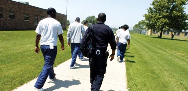 Youths, escorted by a youth supervisor, walk to their classroom building at the Illinois Department of Juvenile Justice Center in Joliet. - PHOTO BY ANTONIO PEREZ/MCT
