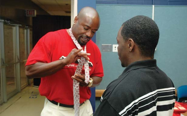 Volunteer Anthony Burke instructs parolees how to properly tie a tie at Summit of Hope. - PHOTO BY GINNY LEE