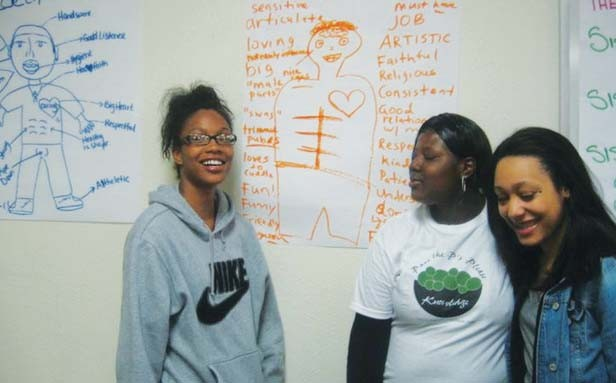 """Ciera Ellis, Tameka Ewing-Kirkwood and Morgan Rochelle in front of an image in which SISTA participants brainstormed characteristics of their """"ideal man."""" - COURTESY SPRINGFIELD URBAN LEAGUE"""