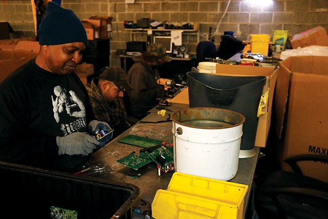 WL Tillman (front) and Ethan Rainey (back) break down circutboards at the deman station (recycle station) in BLH's warehouse connected in the back. Boxes filled with circuit boards flood the processing area of BLH, where employees remove parts that - PHOTO BY BRANDON TURLEY