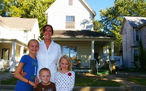 Amber Rigor with her children, Skylar, Kent and Elizabeth, in front of the home she bought from the neighborhood and is restoring on North Sixth Street. - PHOTO BY JOE COPLEY