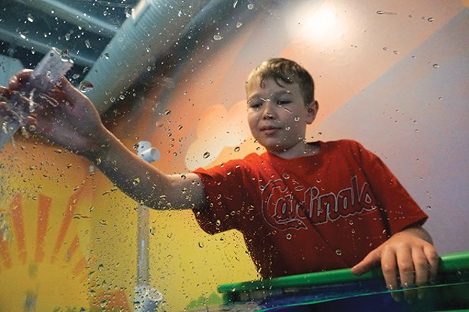 Connor Westlake is engineering a water blaster to rain over Lee, the photographer who is inside the viewing bubble. The Bubble Viewer is part of the Healthy Earth Water table that teaches kids about how water sustains human life and how we need to be good - PHOTO BY LEE MILNER