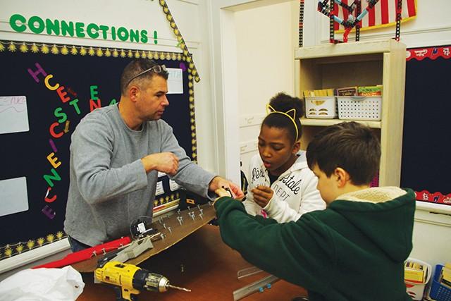 Crawford, Murphy & Tilly engineer Jim Michael works with Dan Hartman's students Kenadie Butler and Colin Furkin on their Rube's plinko board.