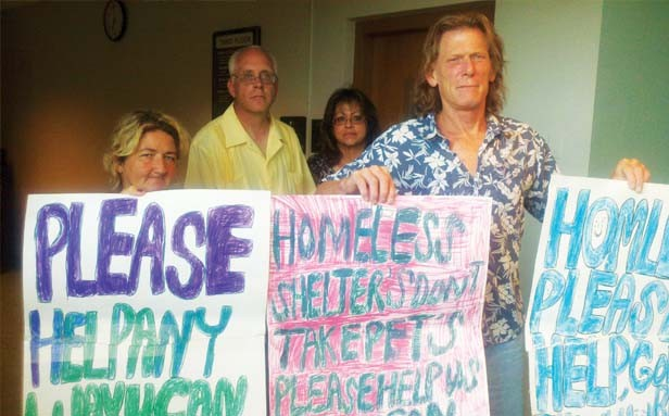 Karen Otterson (left) and Don Norton (right) hold signs used by panhandlers at a July 2 Springfield City Council meeting. The pair sued the city this week in a federal class action lawsuit over the city's anti-panhandling ordinance. - PHOTO BY PATRICK YEAGLE
