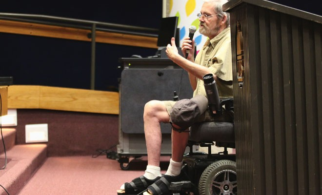 Speaking from his wheelchair, Dennis Garland of Chatham addresses regulators in a May 21 public hearing on medical marijuana, urging the state to roll the program out immediately. - PHOTO BY PATRICK YEAGLE