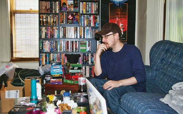 Jones works from a living room that contains as many VHS tapes as DVDs. - PHOTO BY BRUCE RUSHTON