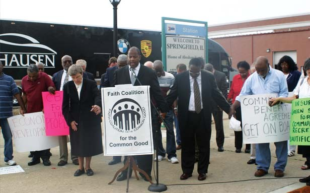 Pastor T. Ray McJunkins leads prayer after calling on local and state officials to sign Springfield agreement. - PHOTO BY HOLLY DILLEMUTH
