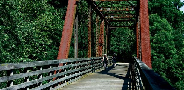 Two cyclists cross a former railroad bridge-turned-bikepath on the Lost Bridge Trail. - PHOTO BY PATRICK YEAGLE