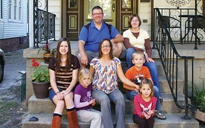 Ryan and Dawn Mobley with their five children – Hannah, left, Rachel, Ellie, top, Aiden and Lydia, front. The Mobleys bought their Sixth Street home from Enos Park Development a year ago and have been restoring it since, using some contractors and - PHOTO BY JOE COPLEY