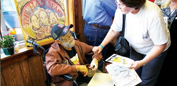 Bob signing his artwork and saying goodbye to people at his last art show at the Cozy Dog. - PHOTO BY B. DAVE HINE