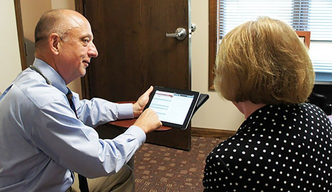 Caption: Dr. Craig Backs reviews test results with a patient at his office in Springfield. - PHOTO COURTESY CRAIG BACKS.