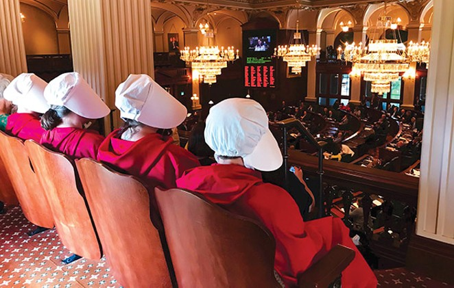 Women dressed as Handmaids, characters from Margaret Atwood's dystopian novel, The Handmaid's Tale, watch as Rep. Kelly Cassidy, D-Chicago, presents her  arguments in favor of the Reproductive Health Act on the floor of the House on Tuesday, - PHOTO CAPITOL NEWS ILLINOIS PHOTO BY REBECCA ANZEL