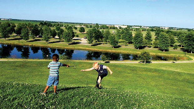 """M and a friend take a quick break from rolling down the hill to """"joust"""" at Centennial Park. - PHOTO BY JESSICA HANDY"""
