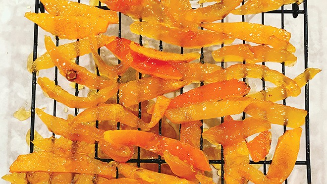 Candied orange peels cooling on a rack.