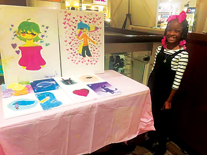 Nine-year-old Janiyiah Green shows off her work at one of The Rainbow Room's art sales. - PHOTO COURTESY THE RAINBOW ROOM