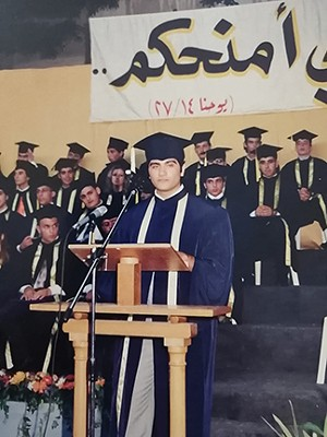 """Nabih Elhajj delivering high school commencement address at Sacred-Heart Beirut, 2005. The banner in the background, written in Arabic, quotes John 14:27: """"Peace I leave with you."""" - PHOTO COURTESY NABIH ELHAJJ"""