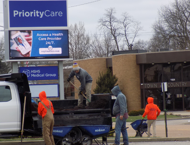A landscaping crew works outside an  HSHS Medical Group clinic as 5 p.m. draws near. - BRUCE RUSHTON