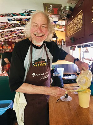 Peter Glatz mixes up some aioli in the school bus he renovated several years ago. - PHOTO BY ANN SHAFFER GLATZ
