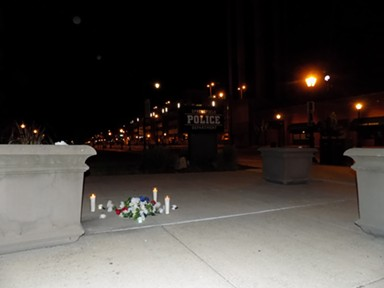 Hours after protesters departed, candles lit in memory of George Floyd outside Springfield police headquarters burned strong as dawn approached. - PHOTO BY BRUCE RUSHTON