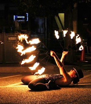 Severyn Beekman dances with fire during the Mardi Gras themed party on Adams Street on July 4. - FACEBOOK.COM/DRMRDREAMER