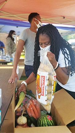 Teresa Haley goes through a box of produce at a recent NAACP food drive in Springfield. - PHOTO BY RACHEL OTWELL