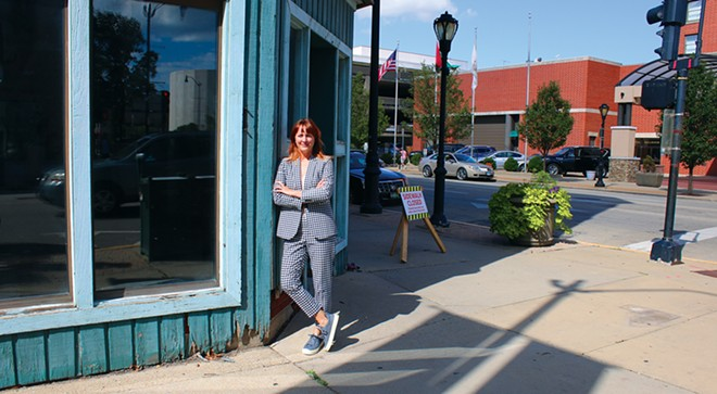 Lisa Clemmons Stott, executive director of Downtown Springfield Inc., has lately been fielding lots of calls from entrepreneurs with ideas for redeveloping downtown property. Here she stands at Seventh and Adams in front of a building that was once the home of Harry S. Clayton Furniture and, more recently, Jade's Emporium. The building has been purchased by new owners with plans to convert the upper stories to 10 new apartments. - PHOTO BY JOSEPH COPLEY.