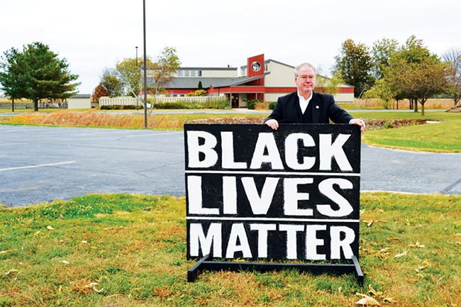 Martin Woulfe stands outside ALUUC, where he regularly replaces Black Lives Matter signs stolen from the congregation's lawn. - PHOTO BY ANGELA AZNARTE