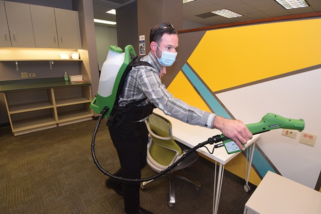 """Clean Impact Commercial Cleaning owner Kirk Kellus uses a """"Ghostbusters""""-looking electrostatic machine to sanitize the Innovate Springfield offices after hours. - PHOTO BY DAVID BLANCHETTE"""