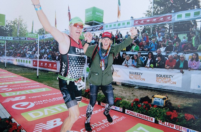Steve O'Connor crosses the finish line at the DATEV Challenge Roth 2019 triathlon in - Roth, Germany, in July 2019, joined by - his wife, Carol.