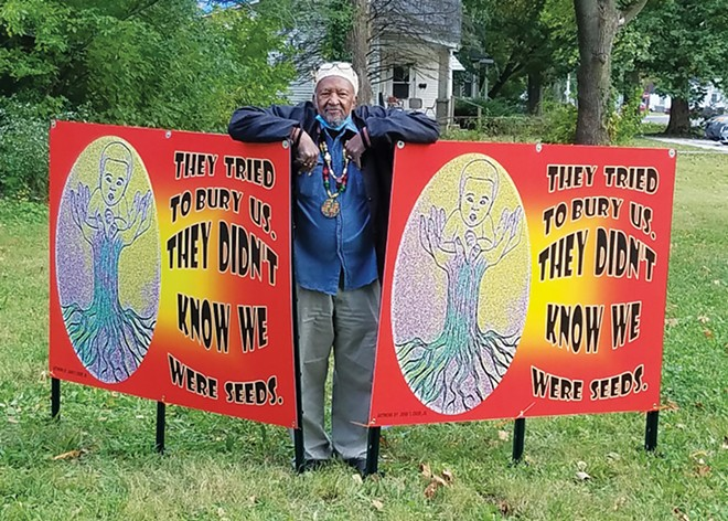 John Crisp Jr. stands with signs he created for the SEAP project, located at the intersection of South Grand Avenue and 14th Street. - PHOTO COURTESY OF SHATRIYA SMITH.