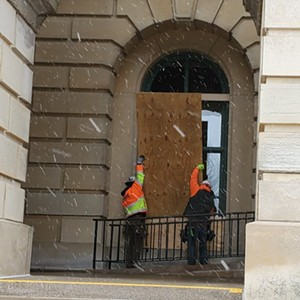 Workers installed plywood on certain Capitol windows on Friday. - RACHEL OTWELL