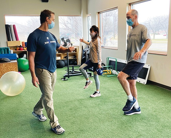 Chad Marschik, owner of Body Symmetry, conducts a personal training session with Keith and Lisa Wichterman.
