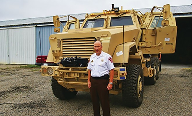 Sangamon County Sheriff Jack Campbell in 2014 with an armored vehicle that now belongs to the LaSalle County sheriff's office. - PHOTO BY BRUCE RUSHTON