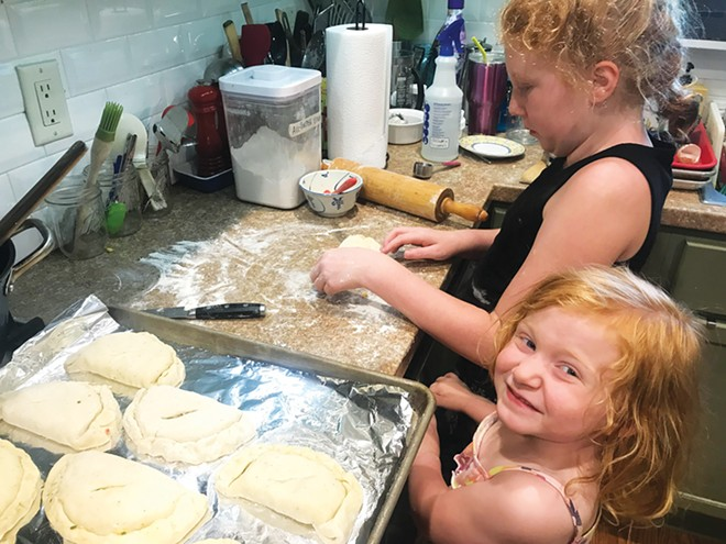Elizabeth Meyer helps her big sister, Maddie, make savory sweet corn and ham turnovers. - PHOTO BY ASHLEY MEYER