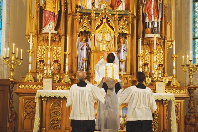 The Rev. Trenton Rauck elevates a chalice for consecration during a Latin Mass at Sacred Heart Catholic Church as servers lift his chasuble vestment. - PHOTO BY SCOTT REEDER