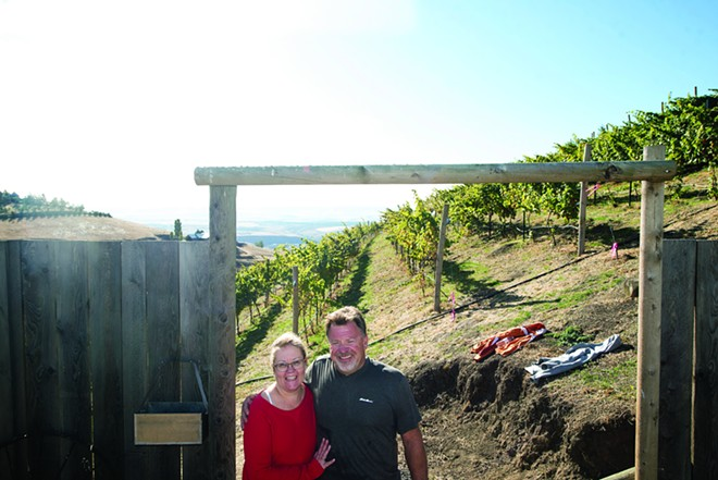 Becky and Stuart Davis, owners of Spiral Rock Vineyard, pose for a portrait at the entrance to the vineyard in Lewiston. - PETE CASTER